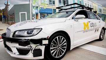 White self-driving sedan drives through MCity