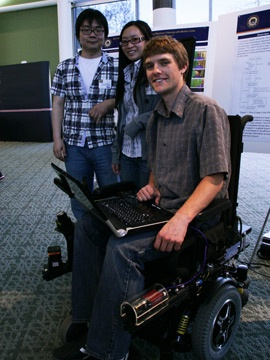 Students show off a modified wheelchair created as part of a project in Hierarchical Robotic Mapping